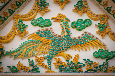 Beautiful stucco of the gable wall with yellow swan decorated with seashells and green tiles in Thai temple.