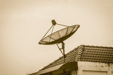 Black satellite disc on rooftop of the house, development of communication concept.