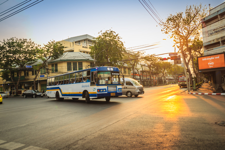 Bangkok, Thailand - March 2, 2017:  Local bus and cars in traffic passes through a busy junction during sunset in Bangkok, Thailand. Editorial