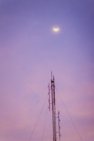 View of the moon on the dusk sky and the folded dipole radio antenna for telecommunications with colorful sky background. Silhouette amateur radio antenna tower in dramatic sky background.