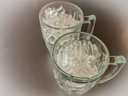 Small cylinder shaped of ice in the glass jug put on the steel table that prepared for pour beverage in it. Stock fotó