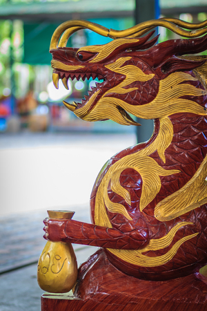 Wooden carving of dragon chair holding rich money bag in the public park. Stock Photo