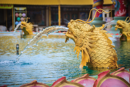 Statue of Chinese dragon fish spraying the water at the fountain in Chinese temple Stock fotó
