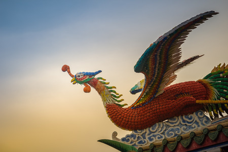 Soft focus view of Chinese phoenix statue on the roof in Chinese temple with dramatic sky background. Stock Photo
