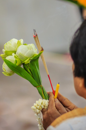 Close up people hands holding incense sticks, candle, lotus flower and garland while making merit for worship ceremony.