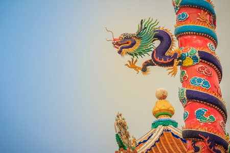 Colorful statue of Chinese dragon wrapped around red pillar. Beautiful statue of dragon carved around temple pole in Chinese public temple.
