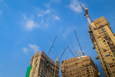 View of luffing jib tower crane at high rise building construction site project. Skyscraper building under construction with the tower cranes on top under blue sky background. Stock Photo