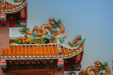Beautiful large grimace dragons crawling on the decorative tile roof in Chinese temples. Colorful roof detail of traditional Chinese temple with dragon statue on blue sky background. Stock Photo