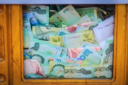 Thai banknotes money in the wooden donation box at the Buddhist temple. Monetary donations can be tax deductible. Stock Photo