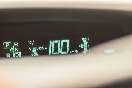 Modern digital mileage odometer and speed meter on dashboard when speed 100 kmh.
