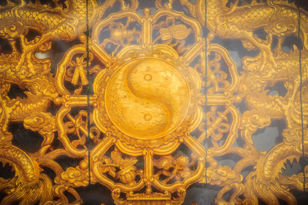 Golden symbol of Yin - Yang on the wall of Chinese temple in Thailand. Stok Fotoğraf