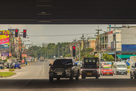 street lamp: Chonburi, Thailand - May 23, 2017: The opposite cars are turning right while the going direct cars are waiting for red lights at the intersection.