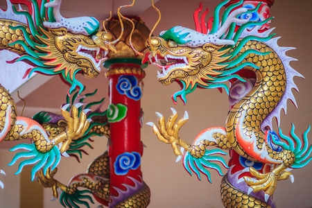 glorify: Colorful statue of Chinese dragon wrapped around red pillar. Beautiful statue of dragon carved around temple pole in Chinese public temple.
