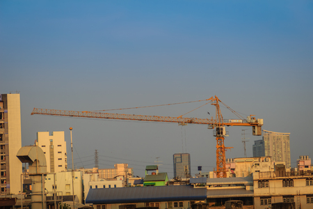 light duty: Large scale condominium construction site with the luffing jib tower crane, new hi-rise buildings growing up into the sky in a densely populated city of Bangkok, Thailand. Stock Photo