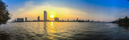 waterfront property: Panorama view of Chao Phraya river during sunset with high-rise condominium and buildings under construction in blue and yellow sky background. Silhouette riverfront view of real estate development.