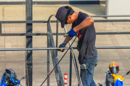 Bangkok, Tailandia - 8 marzo 2017: Un uomo è saldato ad una struttura del tetto d'acciaio del garage di parcheggio senza attrezzatura protettiva.