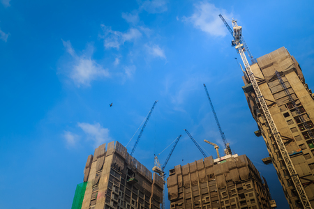 View of construction of multi-storey residential building. Condominium under construction with the luffing jib crane. High-rise skyscraper building construction site with crane against bright blue sky