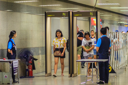 Bangkok, Thailand - April 23, 2017: Passenger is walking pass through the security staff with metal detector arch and full body scanner before access to the subway station under anti-terrorism policy.