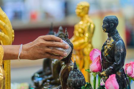 毎年 4 月 13 日毎年恒例の儀式のソンクラン祭りで仏像に儀式を入浴中のタイ人の手を閉じます。仏教のタイの新年の間にメリットを得るために仏像