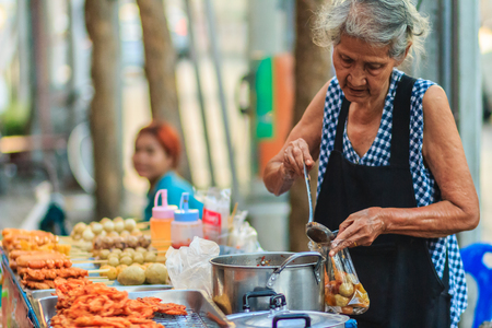 fish vendor: Bangkok, Thailand - April 23, 2017: Unidentified old woman street vendor is selling fried meat balls to her customer.
