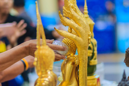 Close up hand of Thai people while bathing rite to buddha images in Songkran festival on the April 13 annual ritual every year. Buddhist is bathing a Buddha statue to gain merit during Thai New Year. Stock Photo