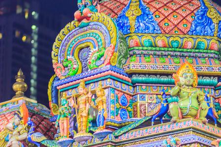 Colorful night view of indian gods sculpture at Sri Maha Mariamman Temple, also known as Maha Uma Devi temple, the public hindu temple in Silom, Bangkok, Thailand. It known as Wat Khaek Silom. Stock Photo