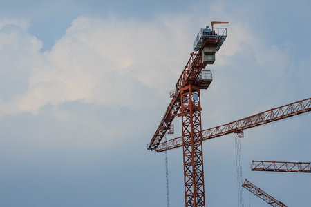 Yellow luffing jib tower crane against blue sky.