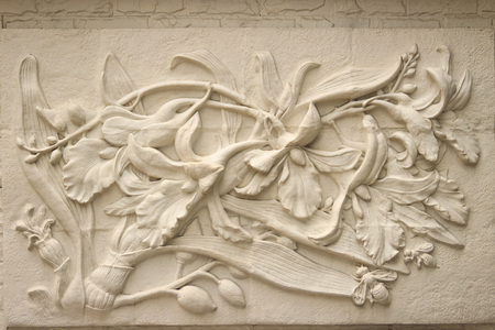 Beautiful white Java stucco patterned on the boundary wall. Vintage white wall bas-relief stucco in plaster, depicts Lotus flowers background. 新聞圖片