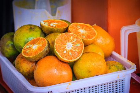 Organic oranges and sliced oranges with jar squeezer prepared for making orange juice for sale in the street fruit shop. Stock Photo
