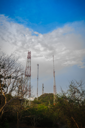 Telecommunication towers on the summit of the hill under cloudy blue sky and covered with colorful fall forest. Stock Photo