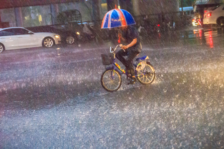 Bangkok, Thailand - July 6. 2017: A man is ridding the bicycle under a heavy rain on the street in the evening. Unidentified man is riding a bicycle and carrying an umbrella in heavy rain on a street. 報道画像