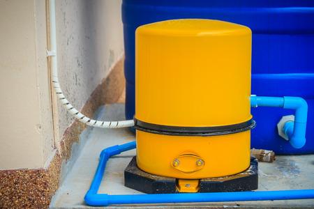Hauswasserversorgungssystem in der Wohnsiedlung, die mit gelber automatischer Wasserpumpe zusammengesetzt ist. Standard-Bild - 85635194