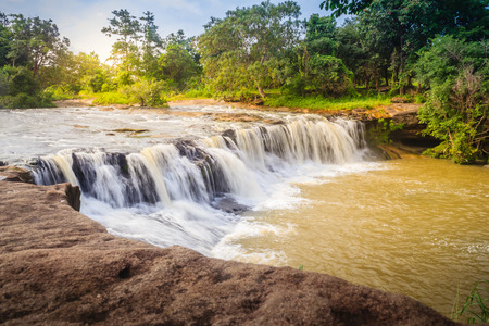 Exotic small waterfall for swimming named Tadton Waterfall in Ubon Ratchathani, Thailand. This cascade falls from a rocky bend like a movie screen through the large rock with large water flow.