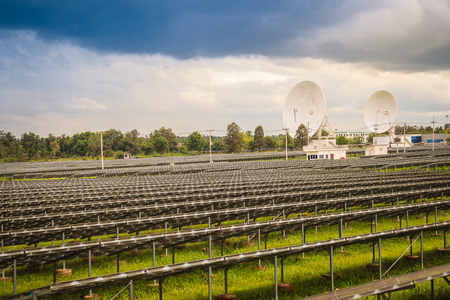 Large scale solar farm with the satellite dishes under dramatic blue and cloudy sky background. Mega photovoltaic power plant in green grass field with two satellite dishes under stormy sky background