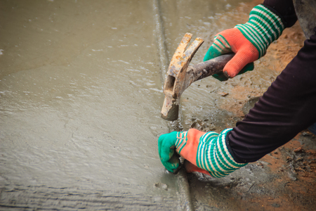 Grooving on concrete pavement by worker used deformed steel bar to stamp on concrete surface before the liquid concrete is solidified. Mason is grouting on concrete slabs to increase adhesion strength Stock Photo