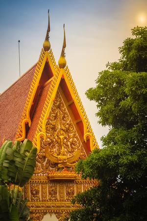 Beautiful sculpture of angel riding garuda holding naga with glass mosaic and other ornamental decoration on the gable end of buddhist church at Wat Phra That Narai Cheng Weng, Sakon Nakhon, Thailand. Stock Photo