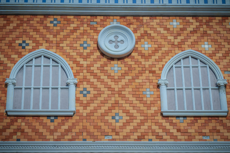 plastered wall: Abstract art of balconies which decorated in circle shape above arch window on brick wall background.