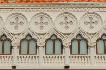 plastered wall: Abstract French balconies which decorated in circle shape above arch door on stucco wall background.