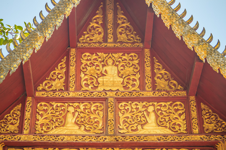 Beautiful craved Buddha with animals in forest patterns on the gables of the Thais northern style church at Wat Chedi Liam, one of the ancient temple in Wiang Kum Kam archaeological area, Chiang Mai.