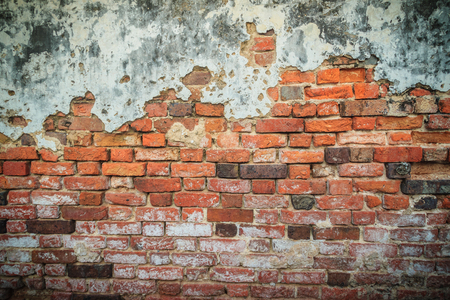 Grungy historical broken brick wall background in sunny summer day. Abstract red brick old wall texture background. Ruins uneven crumbling red brick wall background texture.