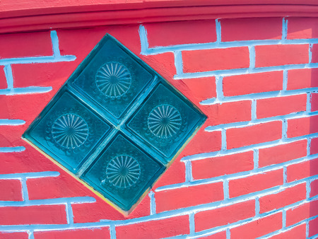 Glass blocks on the red brick wall background. Square glass block installed in a red brick wall.