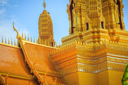 Beautiful golden temple with the golden standing buddha statue in the Ancient City park, Muang Boran, Samut Prakan province.Thailand.