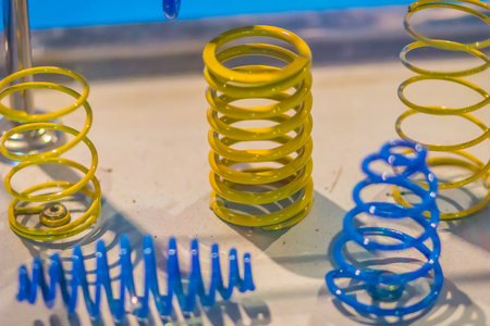 Sample product of blue and yellow metal helical coil springs. Stock fotó