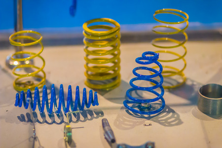 Sample product of blue and yellow metal helical coil springs. Stock Photo