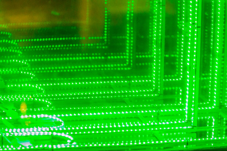 Abstract futuristic green led lights background. Blinking green neon lights unfocused background. Blurry of bokeh light, shimmering blur spot lights on green abstract background.