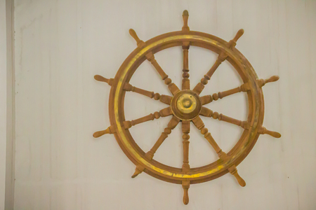 Vintage old wooden ship steering wheel in the public naval museum. Wooden helm of the old battleship.