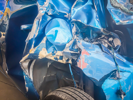 Close-up front of blue new car distorted by accident. Crashed new blue car severely damaged and needs help for move to the garage to repair and call to loss adjuster for car insurance claim. Stock Photo