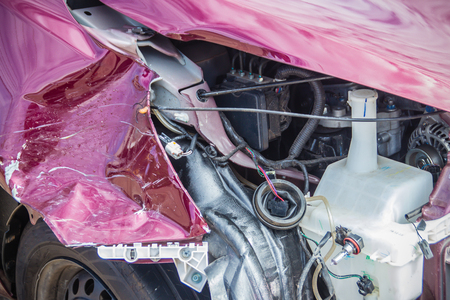 Front of red new car distorted by accident. Crashed new red car severely damaged and needs help for move to the garage to repair and call to loss adjuster for car insurance claim. Stock Photo