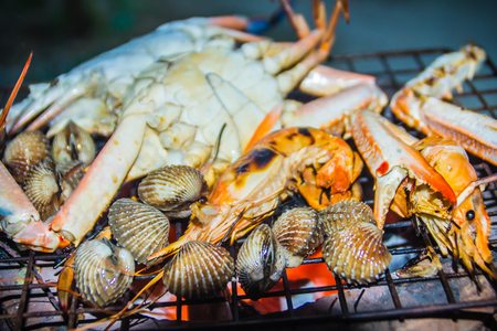Close up grilled crabs and clams on fire charcoal stove at night party. Seafood barbecue party with crabs and clams are grilling on fire. Seafood BBQ concept, selective focus. Stock Photo