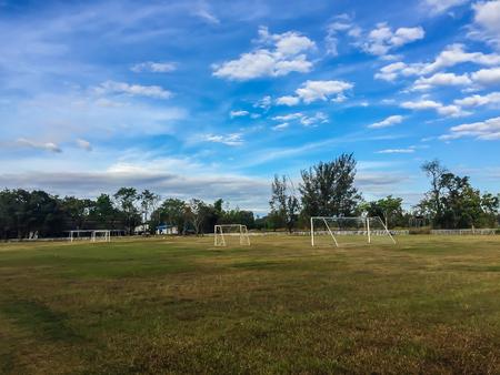 stade de football local avec le but de but et le ciel bleu et les nuages ? ? blancs de fond dans la zone rurale